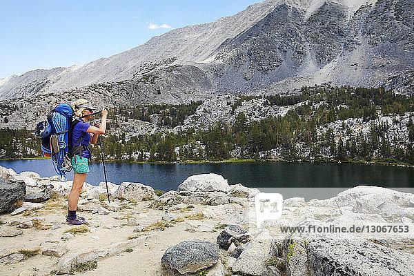 Wanderer steht am Seeufer gegen Berg