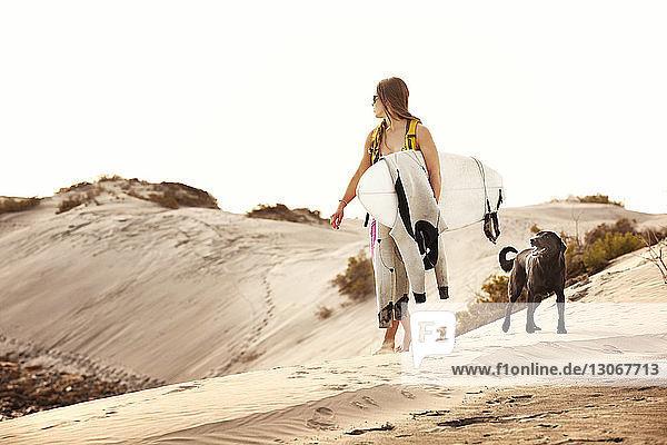 Frau trägt Surfbrett beim Spaziergang mit Hund auf Sand vor klarem Himmel