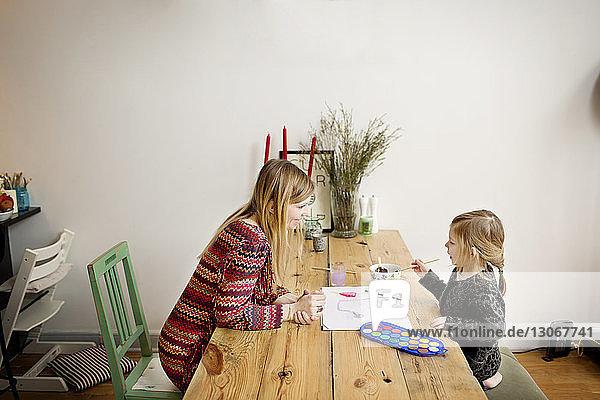 Hochwinkelansicht einer Mutter  die ein Mädchen beim Malen beobachtet  während sie zu Hause am Tisch sitzt