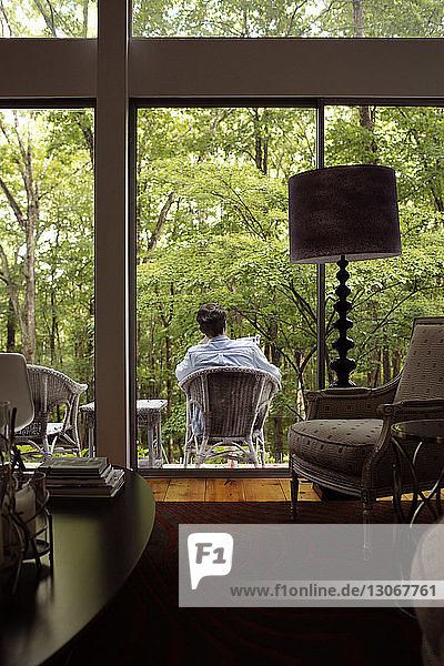 Rear view of man sitting on chair at porch seen through window from house