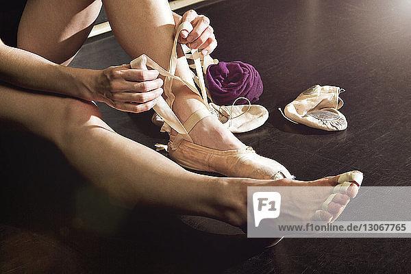 Beschnittenes Bild einer Balletttänzerin beim Schuhbinden im Studio