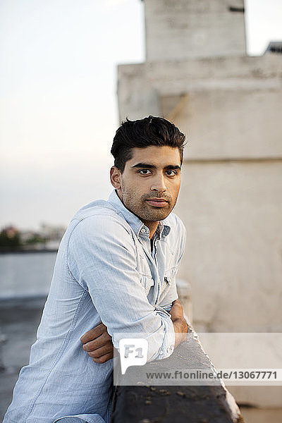 Porträt eines Mannes  der an der Stützmauer einer Gebäudeterrasse gegen den Himmel lehnt