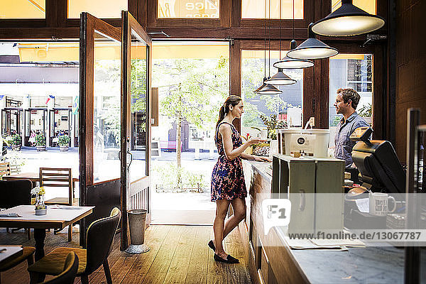 Female customer holding coffee cup while talking to owner at counter in cafe