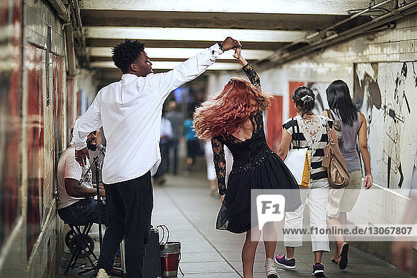 Happy couple dancing while street musician singing in subway