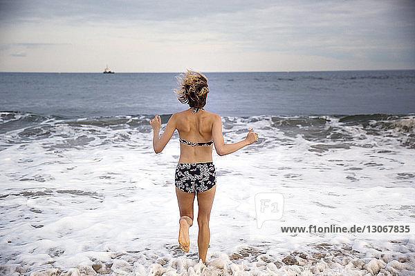 Rückansicht einer Frau  die am Strand an der Küste läuft