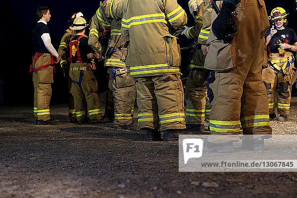 Feuerwehrleute stehen nachts auf dem Feld
