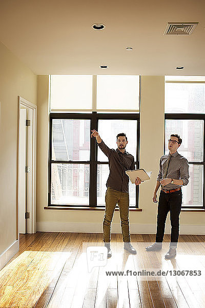 Man with arm raised standing by friend at home