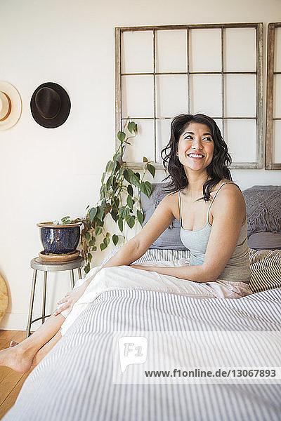 Lächelnde Frau schaut weg  während sie auf dem Bett sitzt