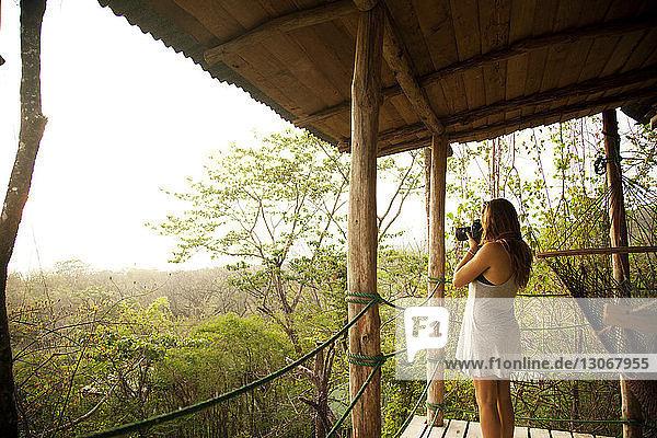 Frau fotografiert stehend auf Baumhaus