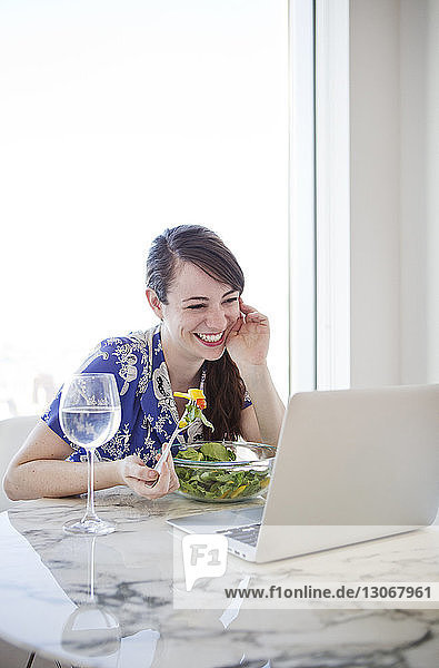 Smiling woman looking at laptop computer while having breakfast