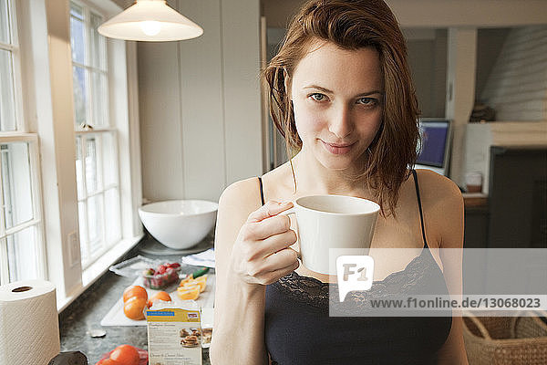 Portrait of woman holding coffee cup while standing in kitchen