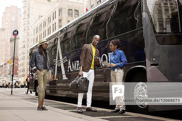 Mann zeigt Mobiltelefon  um den Führer zu führen  während er bei der Frau gegen den Bus auf der Straße der Stadt steht