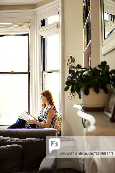 Frau liest Buch  während sie zu Hause auf einem Fensterplatz in einer Nische sitzt
