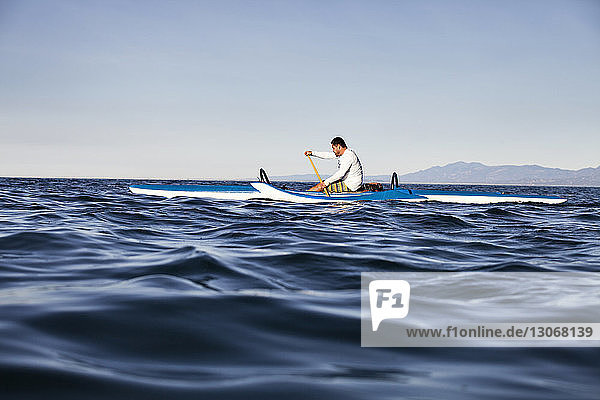 Man rowing outrigger on sea against clear sky
