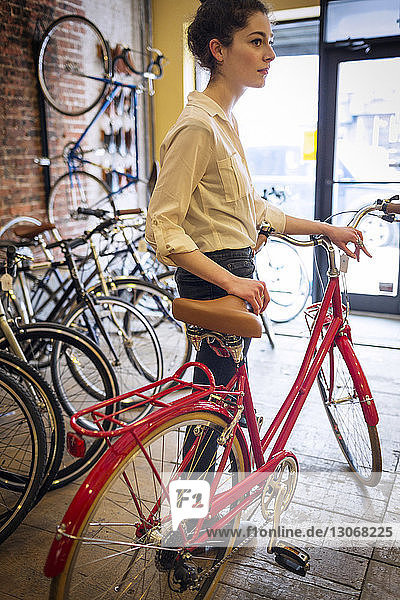 Woman with bicycle looking away while standing in workshop
