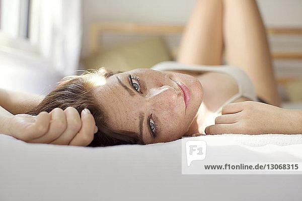 Porträt einer Frau  die sich zu Hause auf dem Bett ausruht