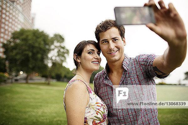 Freunde nehmen Selfie  während sie im Park gegen den Himmel stehen