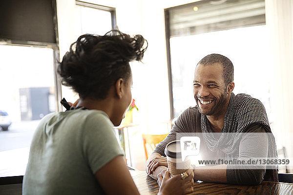 Fröhlicher Mann unterhält sich mit dem Besitzer  der am Tisch sitzt und eine Tasse hält