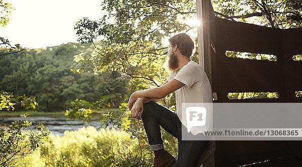 Mann schaut weg  während er sich auf eine Holzkonstruktion stützt