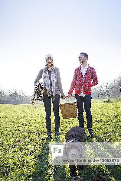 Glückliches Paar steht auf dem Spielfeld vor klarem Himmel