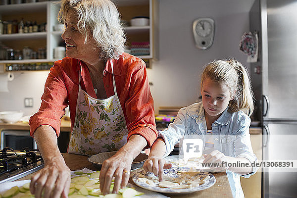 Woman with granddaughter preparing food in kitchen