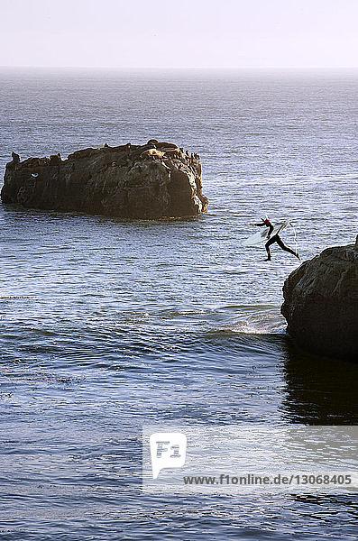 Person mit Surfbrett  die ins Meer springt