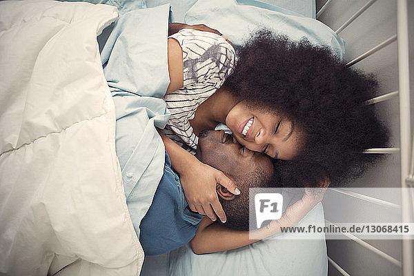 Draufsicht auf ein liebendes Paar  das zu Hause auf dem Bett liegt
