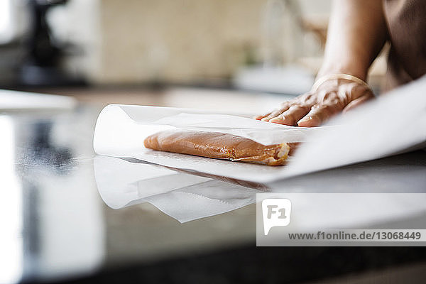 Cropped image of woman wrapping food in paper