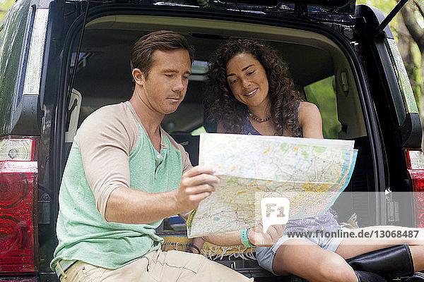 Freunde schauen auf die Karte  während sie im Kofferraum sitzen