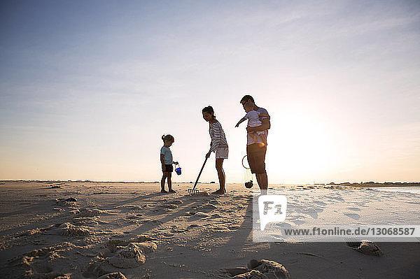 Familie sucht Muscheln am Strand gegen den Himmel