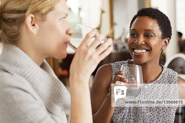 Happy friends enjoying wine at home