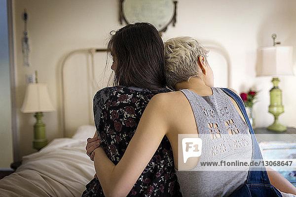 Rückansicht von Freunden  die sich umarmen  während sie zu Hause auf dem Bett sitzen