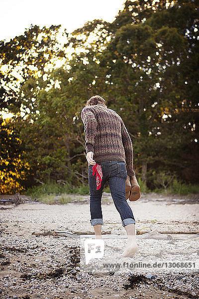Rückansicht eines Mannes  der am Strand am Ufer geht