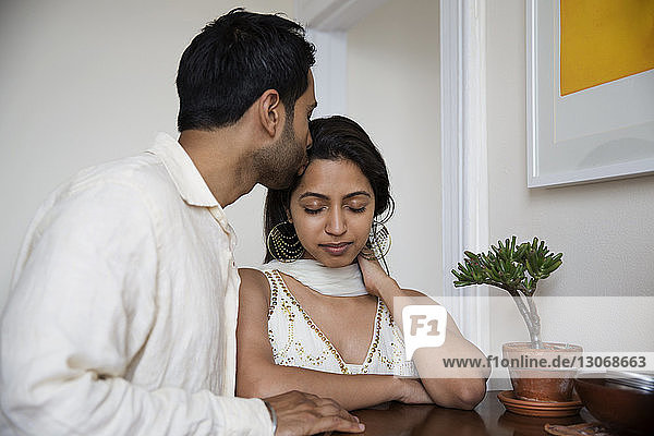 Man kissing woman on forehead while standing by table at home