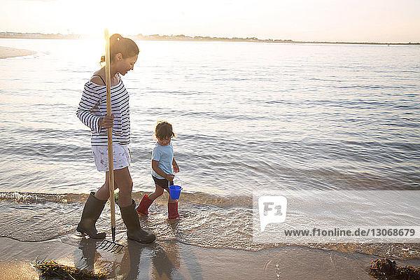 Mutter und Tochter gehen bei Sonnenschein mit Harke und Eimer am Meeresufer spazieren