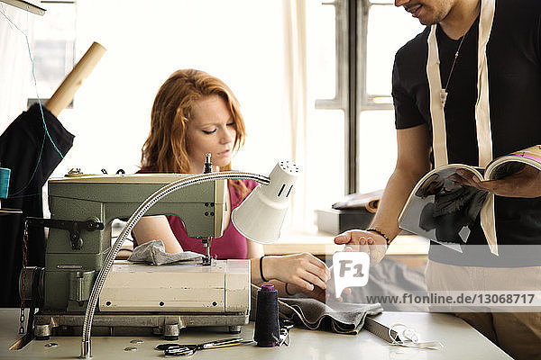 Fashion designer giving spool to coworker while working at workshop