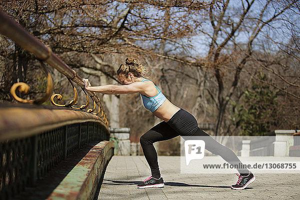 Seitenansicht einer Frau  die im Park an einem Geländer trainiert