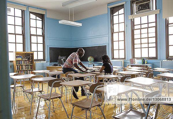 Lehrer und Schüler lesen Buch  während sie im Klassenzimmer sitzen