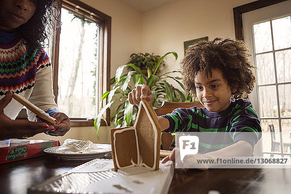 Mother and son making gingerbread house at home