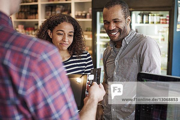 Glückliches Paar schaut sich den Besitzer an  der im Laden eine Kreditkarte einzieht