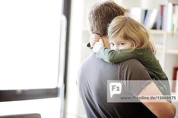 Porträt einer Tochter  die den Vater zu Hause umarmt