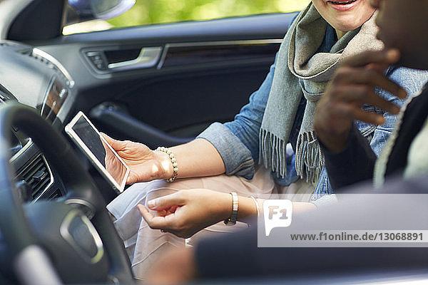Frau zeigt Mann Tablet-Computer  während sie im Auto sitzt