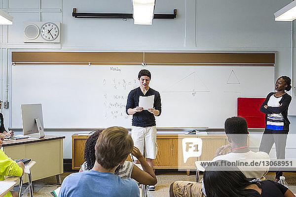 Lehrer betrachtet Schüler während der Unterrichtsstunde im Klassenzimmer beim Lesen