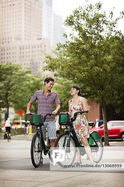 Freunde mit Fahrrad unterhalten sich auf dem Fußweg