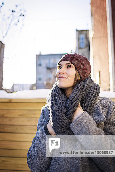 Woman looking away while standing at backyard