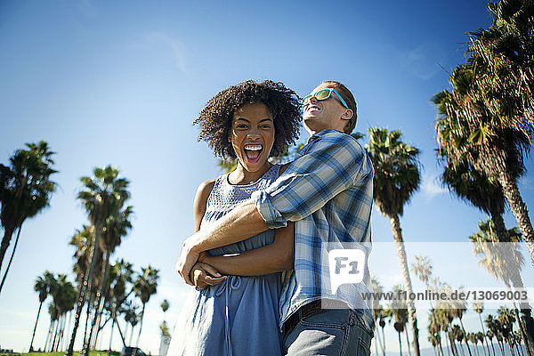 Niedrigwinkelansicht eines Mannes  der eine Frau umarmt  während er gegen den Himmel steht