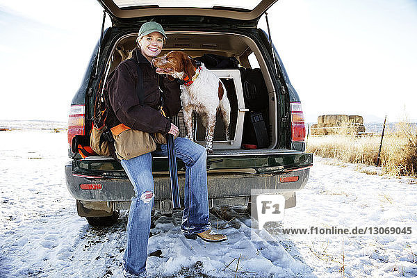 Portrait of female hunter sitting with dog in car trunk