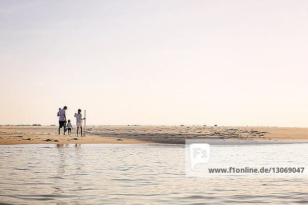 Familie geht am Strand am Meeresufer bei klarem Himmel
