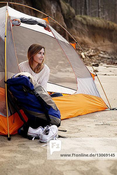 Frau schaut weg  während sie im Zelt sitzt