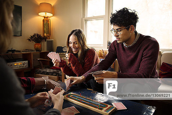 Cheerful friends playing cards while resting in illuminated living room